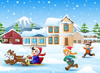 Cartoon boy riding sled on the snowing village with running kids