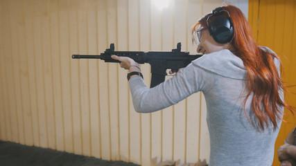 Woman shooting with a Mashin gun in shooting gallery