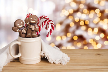 Gingerbread man and candy in dish over abstract holiday background