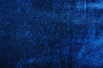 Velvet dress material cloth texture pattern. Blue velvet tailoring stitching concept. Shiny beautiful fashion fabric. Shiny clothing material sample.Creased fabric. Fashion fabric macro photo.