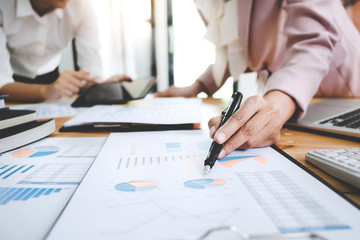 Business women analysis investment perform data document and calculating a valuation number