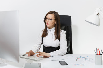 Beautiful serious and engrossed brown-hair business woman in suit and glasses sitting at the desk, working at computer with modern monitor with documents in light office, on white background