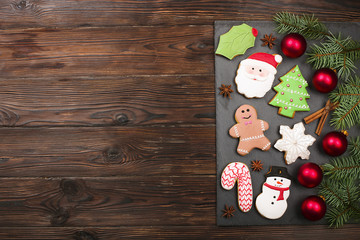 Christmas gingerbread funny cookies with fir branches, cinnamon sticks, candy cane and decoration flat lay on wooden table, copy space. Christmas holiday sweets food