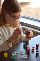 Girl making do-it-yourself toys, paints a pottery clay toy with gouache. Indoors creative leisure for children. Supporting creativity, learning by doing, DIY project, hand craft. Master class of art.