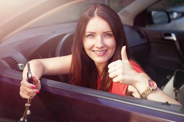 schöne Frau hält Autoschlüssel aus dem Fenster