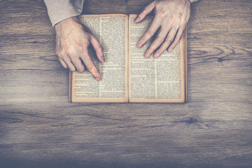 old man hands pointing words on vintage & grunge book