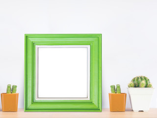 Green wooden frame with cactus in pot on wood table