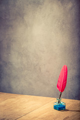 Vintage old red quill pen with inkwell on wooden table front concrete wall background. Retro style filtered photo