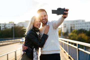 Beautiful young couple making selfie on bridge
