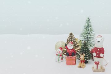 Christmas toy doll,Christmas tree and New Year holidays gift box with decorative ornament on white snow with falling snow effect background.Gifts and congratulations concept.