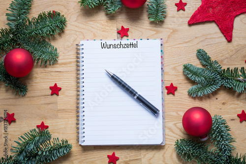 wish list for christmas in german on a notepad with christmas decorations and fir branches on
