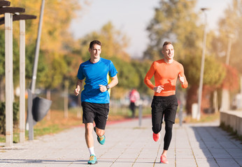 Handsome young men wearing sportswear and running at quay during autumn
