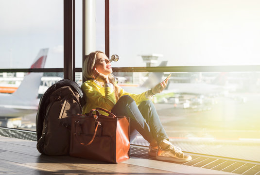 Hipster girl waiting for flight in airport and listening to music