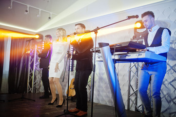Musicial music live band performing on a stage with different lights.