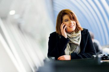 Picture of woman in black coat talking on phone sitting atcafe