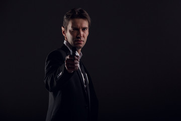 Image of male bodyguard with gun isolated on black background.