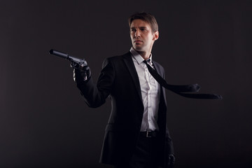 Photo of man with developing tie in leather gloves with gun