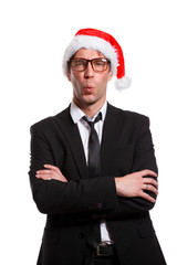 Image of whistling man in business suit, glasses, Santa hat, with his arms crossed