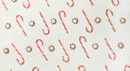 Christmas holiday food pattern. Flat-lay of red candy-cane sticks and star sugar glazed cookies over white background, top view, wide composition. Holiday wrapping paper or wallpaper concept