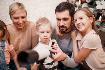 Picture of happy family with telescope on background of Christmas tree