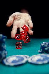 Photo of man throwing red dices on table with chips in casino