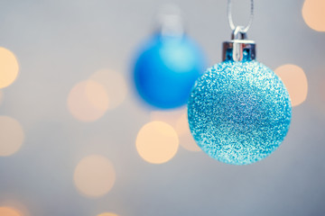 Photo of two Christmas blue balls on gray background with spots.