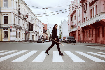 Guitarist in dark clothes crosses the street on the transition
