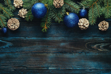 New Year and Christmas decorations Pine tree branches, cones, blue Christmas toys on a wooden background.