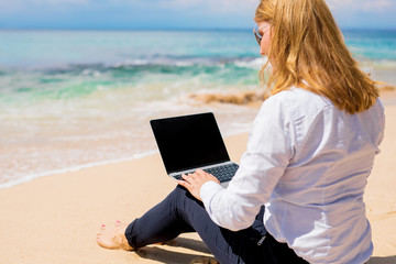 Businesswoman sitting on the beach and working with laptop computer