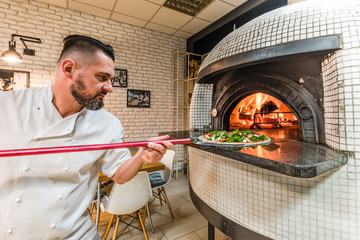 Bearded man baking pizza in woodfired oven