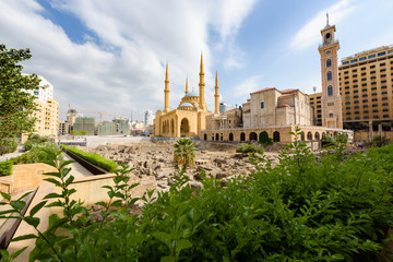 Saint George Maronite Cathedral and Mohammad Al Amine blue Mosque across roman ruins in downtown Beirut, Lebanon.