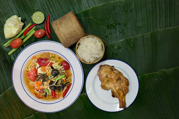 Papaya salad mix with salted crab (Som tum) with grill chicken and sticky rice in bamboo basketry and vegetables on banana leaf Thai food
