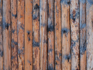 Rustic wooden fence background view. Round brown logs.
