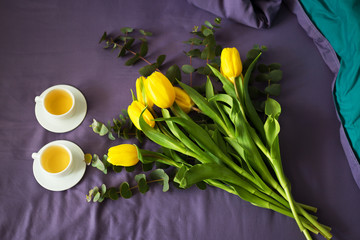 Yellow tulips and two cups of tea in bed, morning