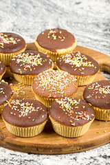 Vanilla cupcakes with chocolate cream and colorful sprinkles
