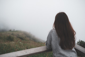 A woman standing alone on balcony looking at white foggy and mountains background