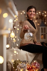 Young woman at fireplace with christmas lights