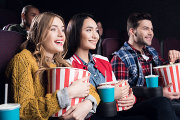 young smiling friends with popcorn watching film in movie theater