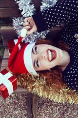 Chica joven y pelirroja tumbada en un banco llevando un gorro de papá noel y cubierta de decoración navideña