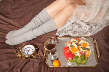 morning Breakfast of a beautiful girl: Cup with fresh hot coffee, fried eggs with tomatoes and greens, candy on a mirrored tray in the bedroom