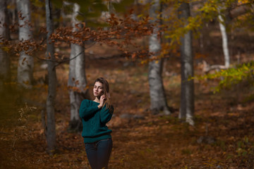 Portrait of young happy woman in casual clothes at the autumn fall forest