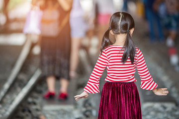 Rear view of modern little girl, standing.