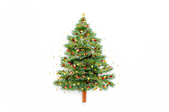 Mini Christmas tree made of fir branch decorated with gold and red confetti on white background. New Year, holiday concept. Flat lay, top view
