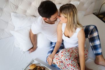 Couple kissing and having breakfast in bed.