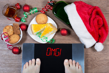 """Female feet on digital scales with sign """"omg!"""" surrounded by Christmas decorations, bottle, glass of alcohol and sweets. Concept of unhealthy lifestyle."""