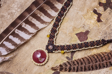 Fotobehang Schip Natural gemstone handmade macrame meterial necklace with wild feather background