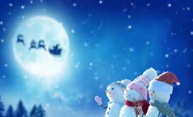 Wall Mural - Merry Christmas and happy New Year greeting card with copy-space.Three snowmen standing in winter Christmas landscape.Winter background