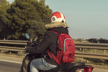 Vintage style motorcyclist driving on the road with red helmet and winter blouse