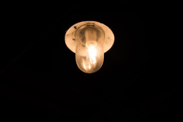 Single illuminated lightbulb with cover surrounded by pitch black darkness