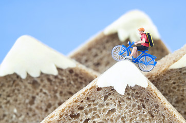 A toy cyclist is taking a ride on mountains, made of healthy rye bread and creamy cheese....